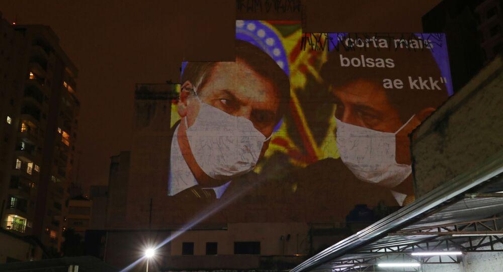 Paulistano projeta imagem do presidente Jair Bolsonaro e de seu ministro da Saúde, Luiz Mandetta, em fachada de prédio durante novo panelaço, em São Paulo, 19 de março de 2020
