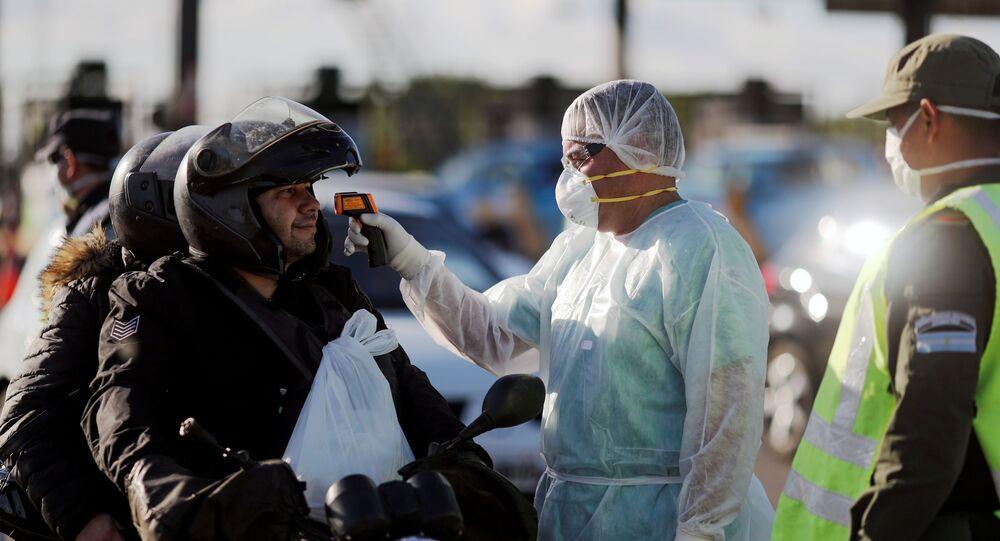 Agente de saúde mede temperatura de motociclistas, em Buenos Aires, Argentina, 19 de março de 2020