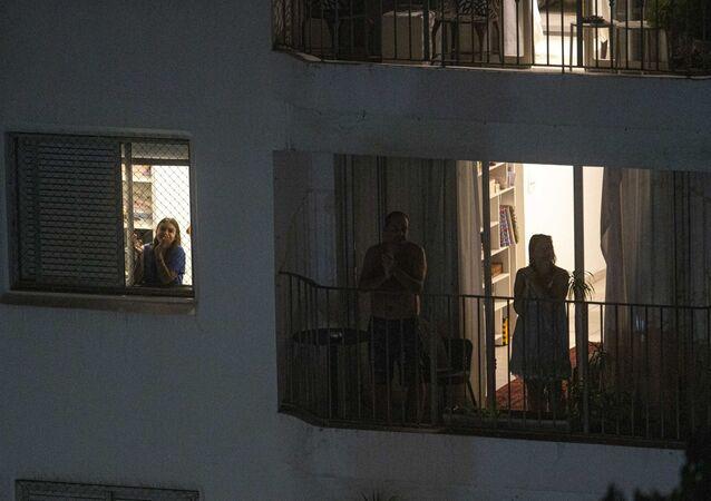 Pessoas saem nas janelas e sacadas de edifícios no bairro de Perdizes, em São Paulo, para realizar uma salva de palmas em homenagem aos médicos que estão atuando nos cuidados aos pacientes que contraíram o novo coronavírus