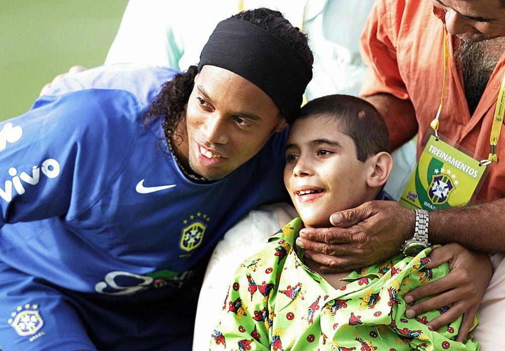 Jogador de futebol brasileiro Ronaldinho Gaúcho posa com fã antes de treinar em Teresópolis, Brasil, em 2005