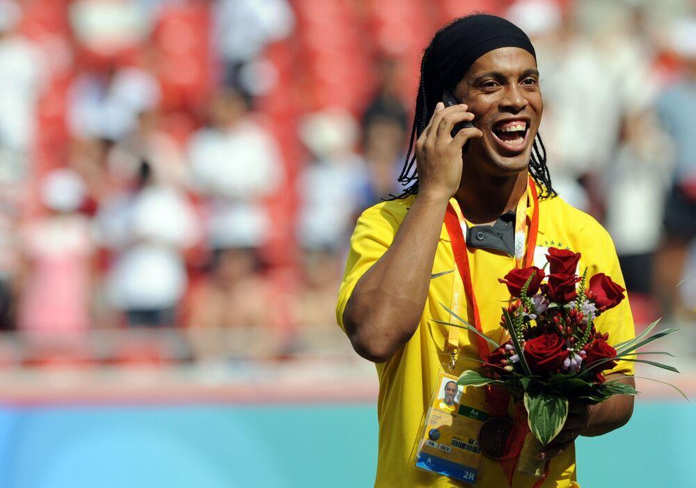Ex-atacante brasileiro Ronaldinho Gaúcho fala ao telefone no Estádio Nacional de Pequim, em 2008