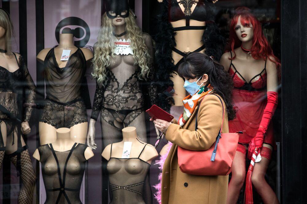 Mulher usando máscara passa ao lado de vitrine de loja de materiais adultos em Pigalle, Paris.