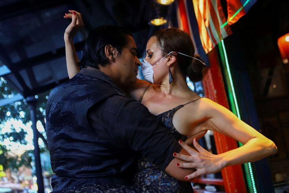 Dançarina de tango Makrina Anastasiadou e seu parceiro bailando El Morocho para o público em um restaurante vazio da capital argentina, Buenos Aires