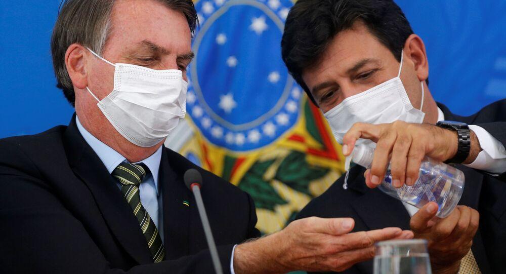 Presidente brasileiro, Jair Bolsonaro, em conferência junto com seu ministro da Saúde, Luiz Henrique Mandetta, passa álcool-gel na mão e usa máscara