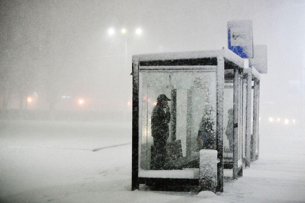 Pessoas esperando transporte público em ponto de ônibus durante nevasca que atinge a cidade russa de Podolsk, na região de Moscou