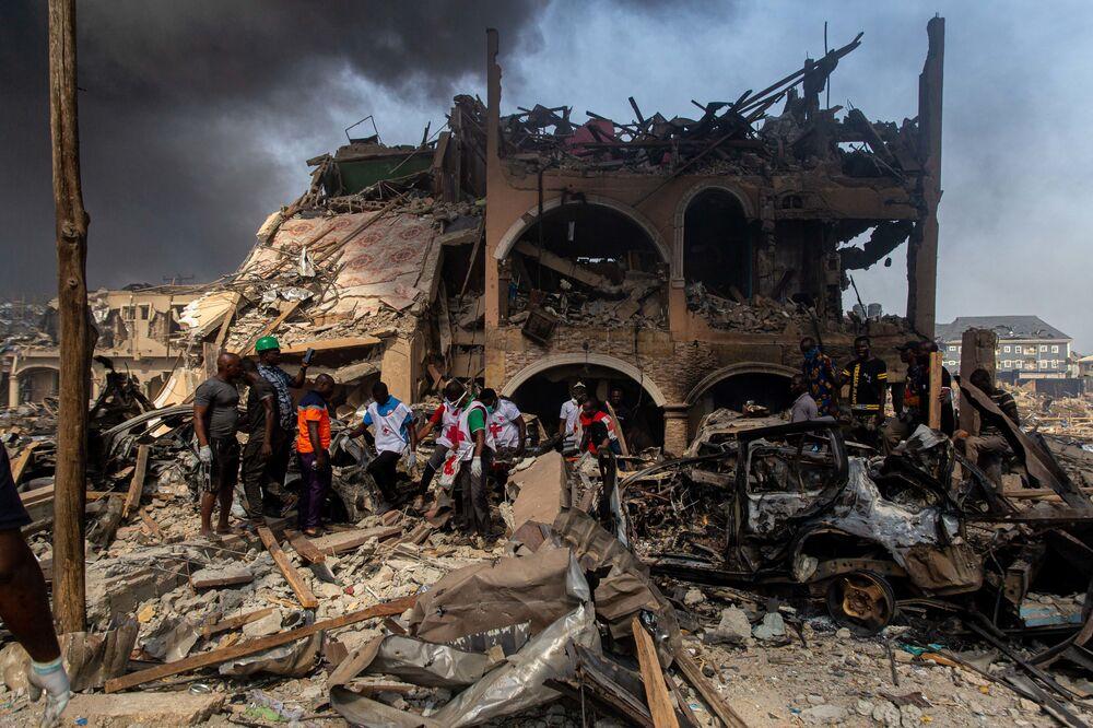 Membros da Cruz Vermelha em operação de resgate após explosão de gás destruir prédios na capital nigeriana, Lagos