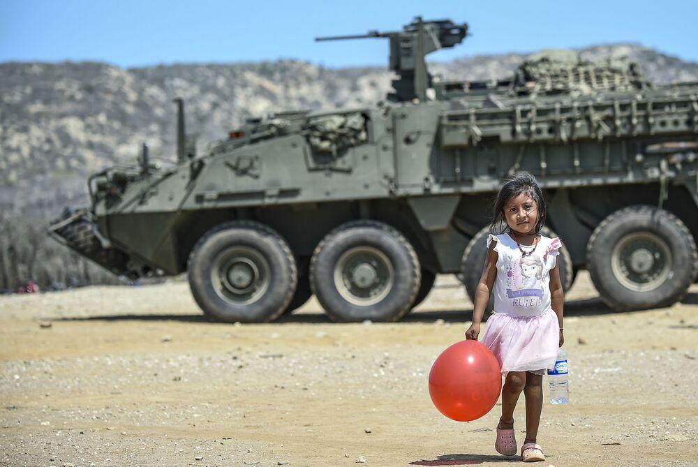 Menina indígena Wayuu passa com uma bexiga vermelha ao lado de um blindado colombiano durante exercício militar realizado no norte do país, na fronteira com a Venezuela