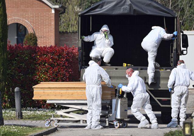 Homens descarregam caixões de pessoas mortas pela COVID-19 em um cemitério no norte da Itália.