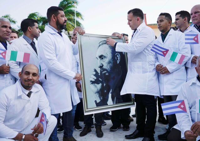 Médicos cubanos a caminho da Itália seguram imagem do falecido presidente cubano, Fidel Castro, durante cerimônia de despedida em Havana, 21 de março de 2020