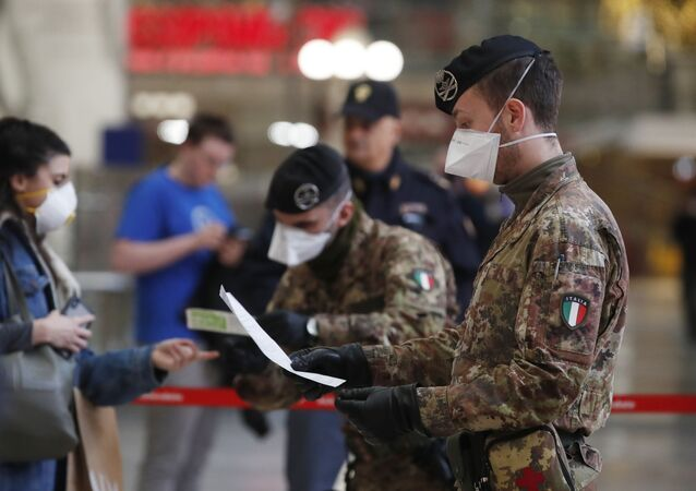 Soldados com máscaras conferem documentos de passageiros antes de embarque em estação de trem de Milão, na Itália