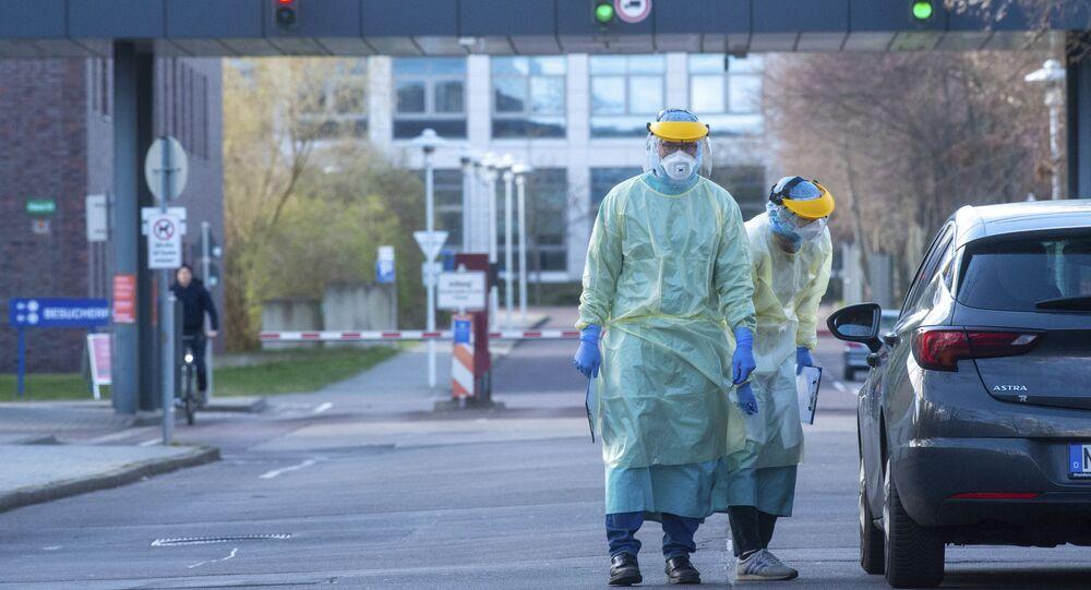 Funcionários com trajes de proteção contra o coronavírus diante de um hospital na Alemanha.