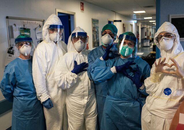 Grupo de enfermeiros com máscara e equipamento de proteção no hospital de Cremona, na Itália