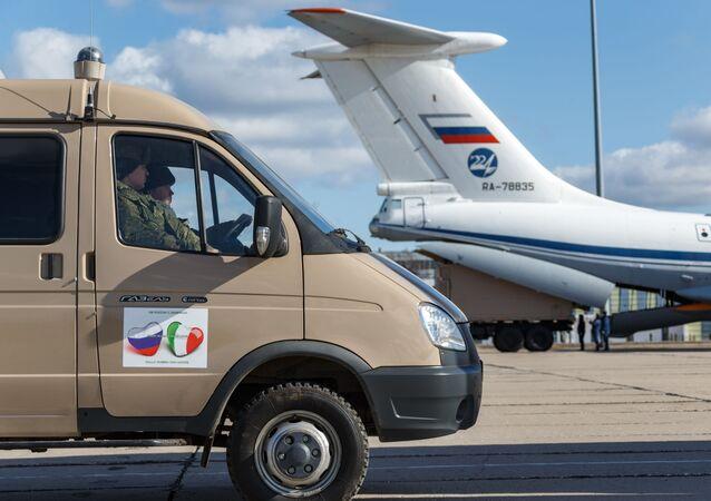Automóvel com suprimentos destinados à Itália se prepara para transferir carga para a aeronave militar Il-76