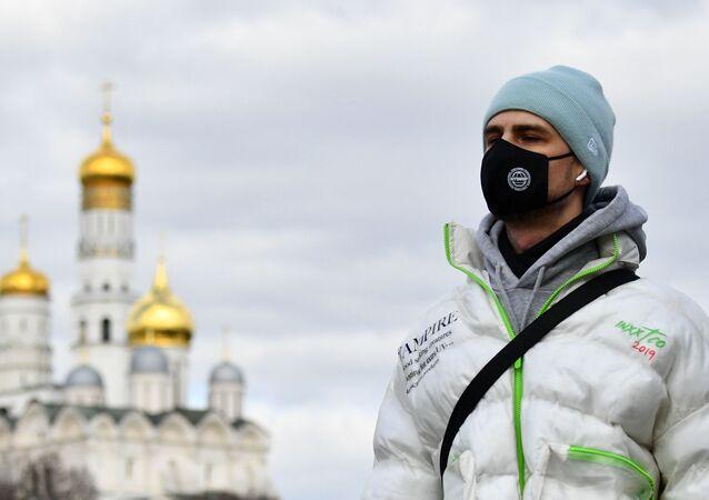 Jovem usando máscara protetora próximo a igreja ortodoxa em Moscou, 21 de março de 2020