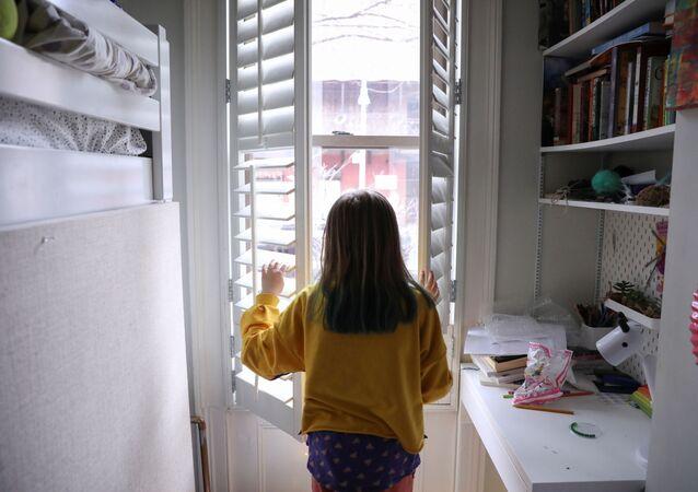 Criança olha pela janela durante quarentena após fechamento de escolas, em Nova York, EUA, 19 de março de 2020