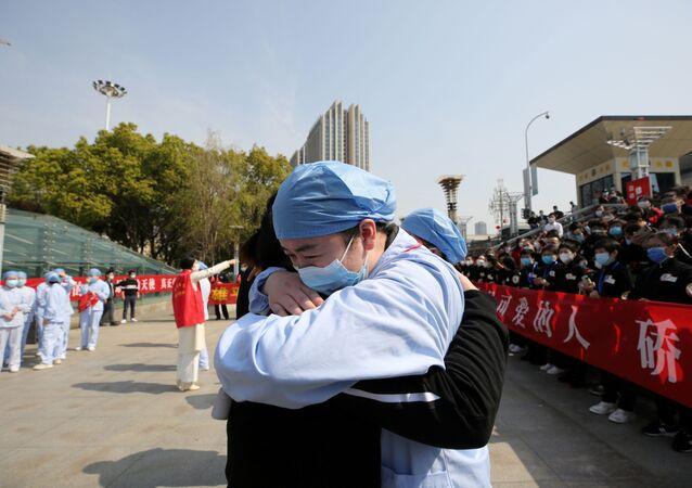 Médicos se despedem em estação ferroviária da cidade de Wuhan, local epicentro do coronavírus, na província de Hubei, China, 19 de março de 2020