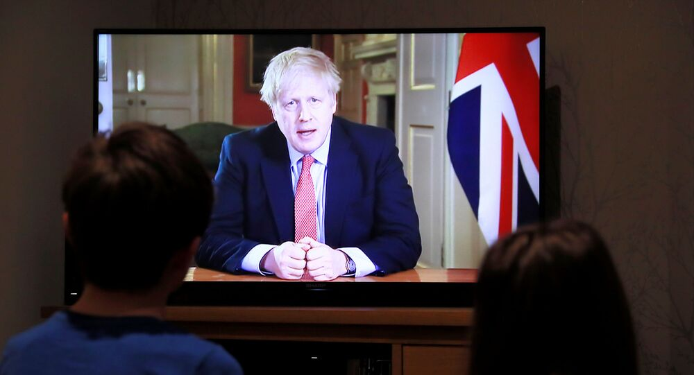 Crianças assistem ao anúncio do primeiro-ministro britânico Boris Johnson sobre a pandemia do coronavírus, em Hertford, Reino Unido, 23 de março de 2020