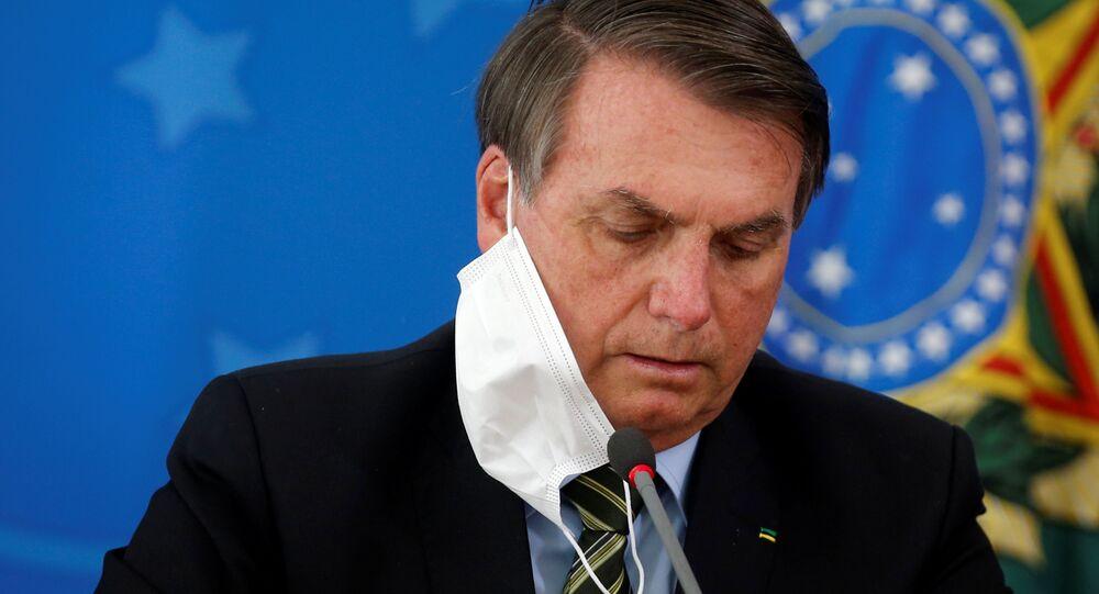 Presidente do Brasil, Jair Bolsonaro, ajeita máscara durante coletiva de imprensa sobre medidas federais para conter coronavírus, Brasília, 18 de março de 2020