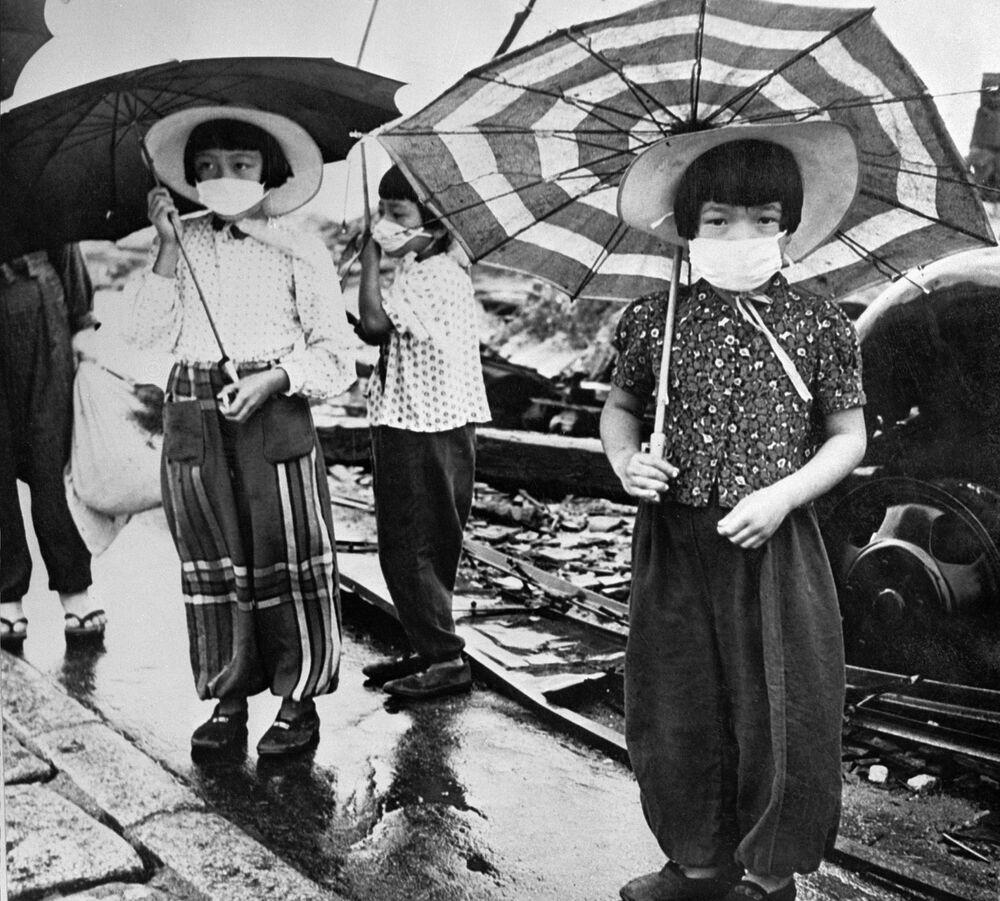 Crianças usando máscaras para se proteger da radiação na cidade devastada de Hiroshima