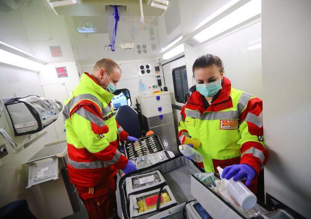 Os paramédicos Jochen e Julia verificam o equipamento de uma ambulância antes do início do seu turno, à medida que a propagação da doença COVID-19 continua, Worms, Alemanha, 24 de março de 2020 (imagem referencial)