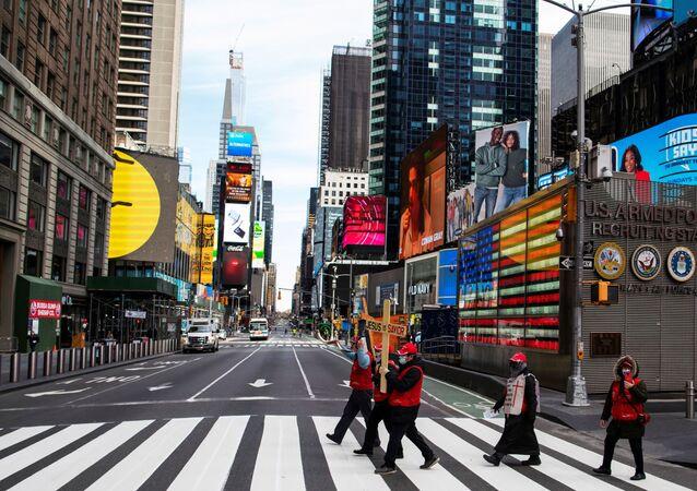 Pessoas caminham pela Times Square enquanto o surto de coronavírus continua em Nova York, EUA, 21 de março de 2020