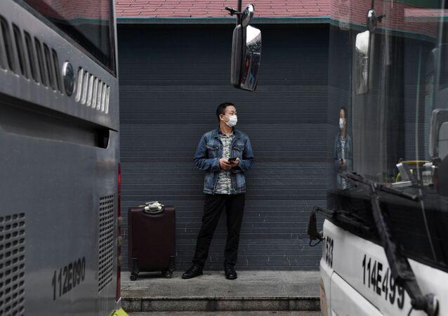 Homem usando máscara protetora em terminal de ônibus na cidade de Wuhan, capital da província chinesa de Hubei, 25 de março de 2020