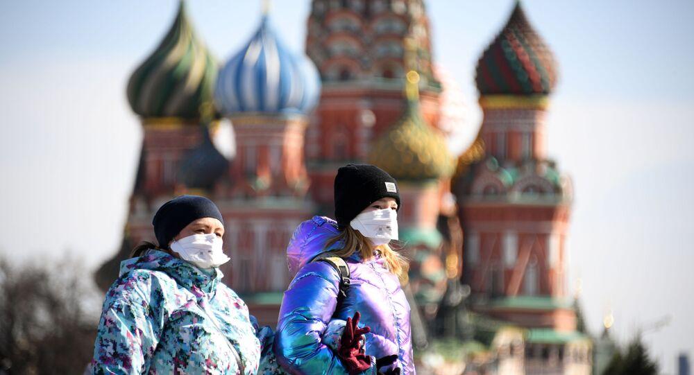 Moças com máscaras andando pela Praça Vermelha, Moscou