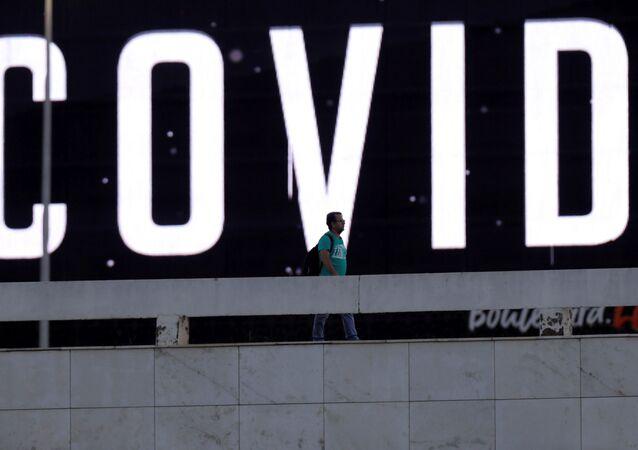 Homem passa por tela LED ao ar livre durante pandemia de coronavírus em Brasília, Brasil, 24 de março de 2020