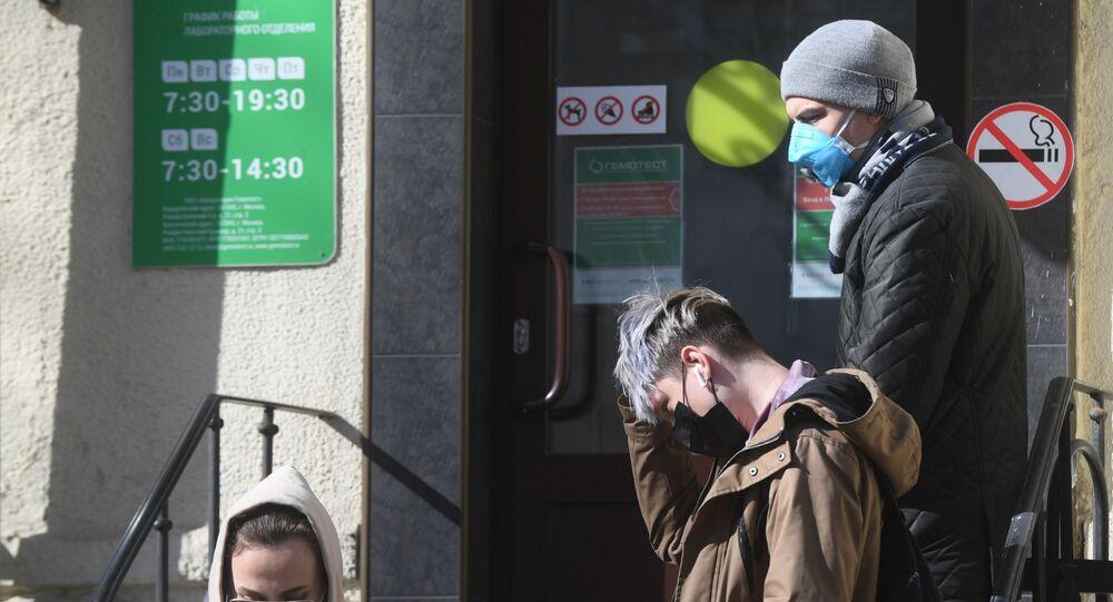 Moradores de Moscou com máscaras na porta de laboratório de análises do coronavírus