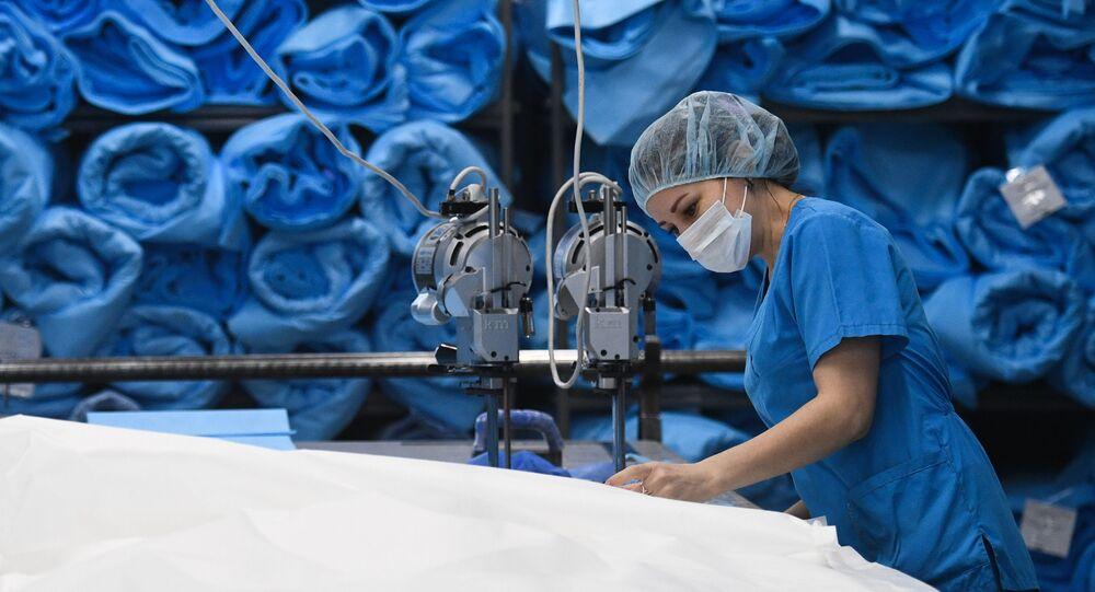 Funcionária de fábrica produz roupas médicas e máscaras de proteção na região de Novossibirsk, na Rússia, 20 de março de 2020