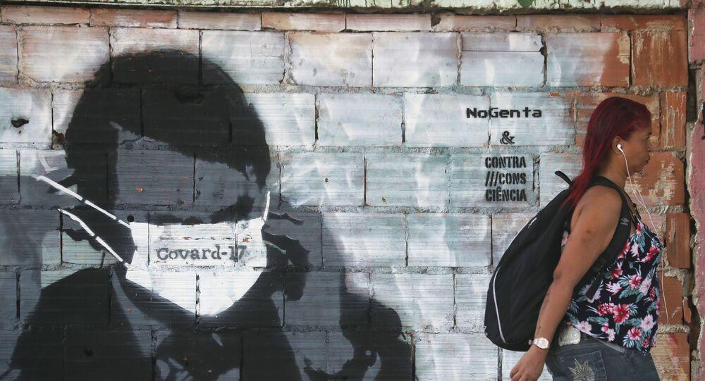 Pedestre passa por muro grafitado no Rio de Janeiro, 26 de março de 2020