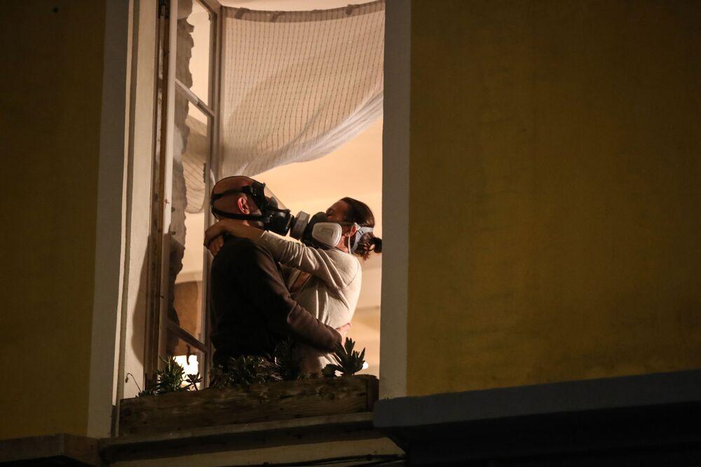 Homem e mulher com máscaras de proteção se abraçam em janela na cidade francesa de Nice, em 24 de março de 2020