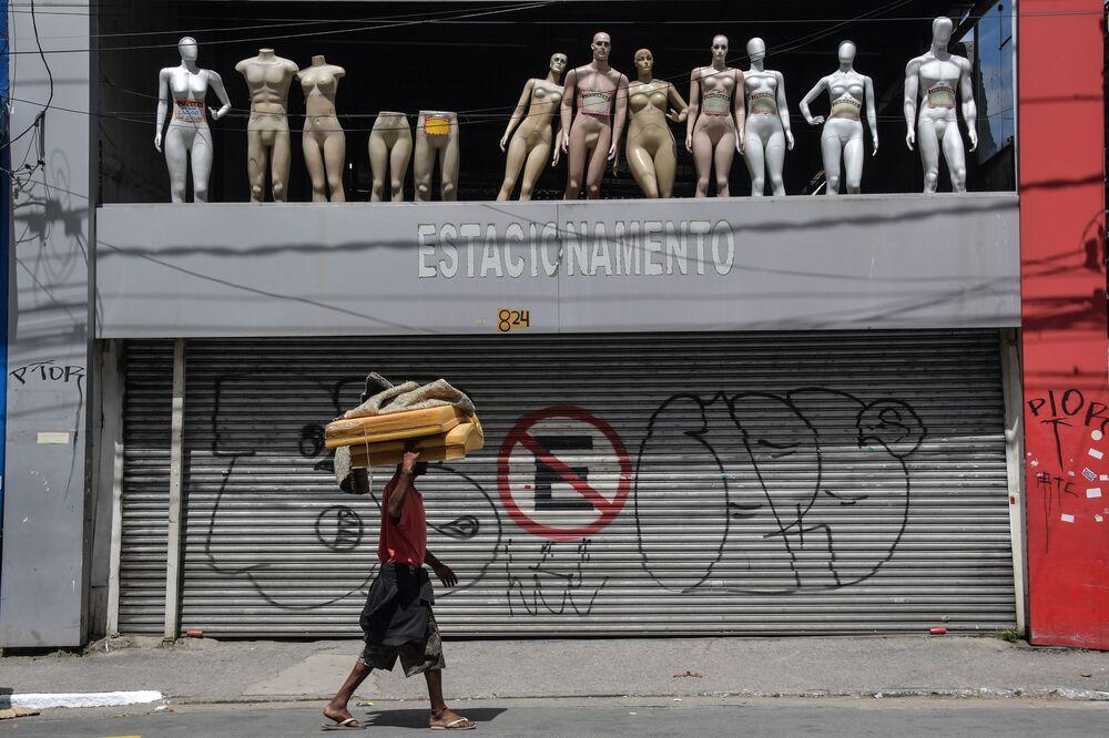 Sem-teto passa por estacionamento fechado e manequins no centro de São Paulo, Brasil, depois que a prefeitura decretou o fechamento de lojas e comércios como medida preventiva contra a propagação do novo coronavírus, 24 de março de 2020