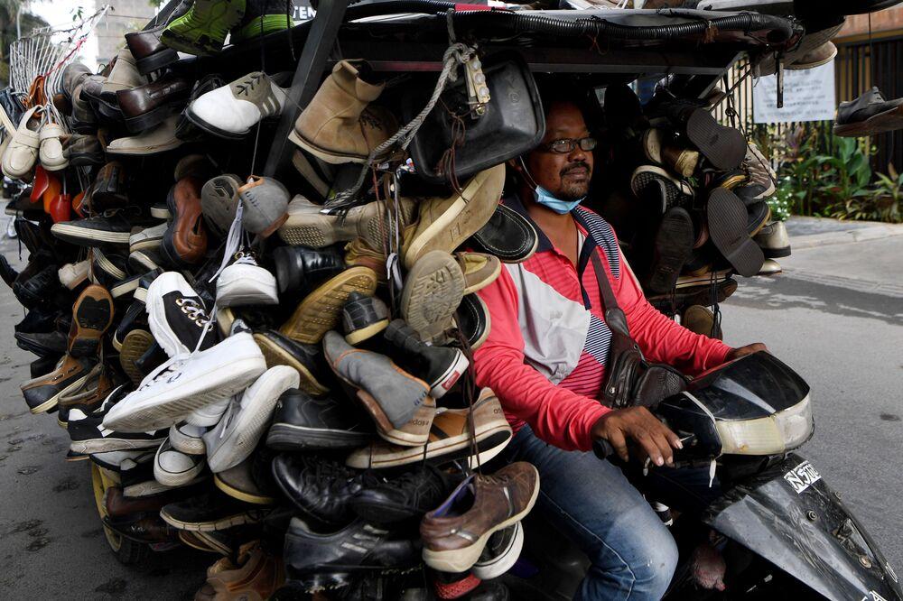 Homem anda de moto transportando sapatos de segunda mão para venda em rua no Camboja, 24 de março de 2020