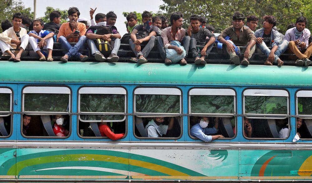 Pessoas viajam em ônibus lotado para retornar às suas casas em meio à pandemia, em Calcutá, Índia, 23 de março de 2020