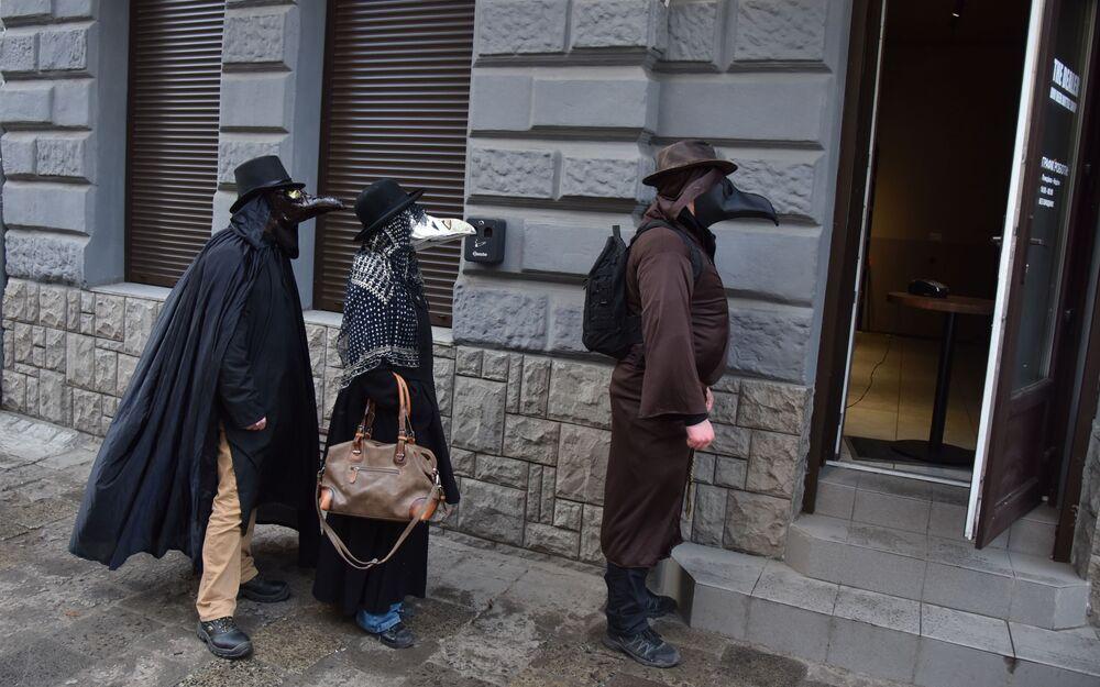 Pessoas fantasiadas caminham em rua durante pandemia de coronavírus, em Lvov, Ucrânia