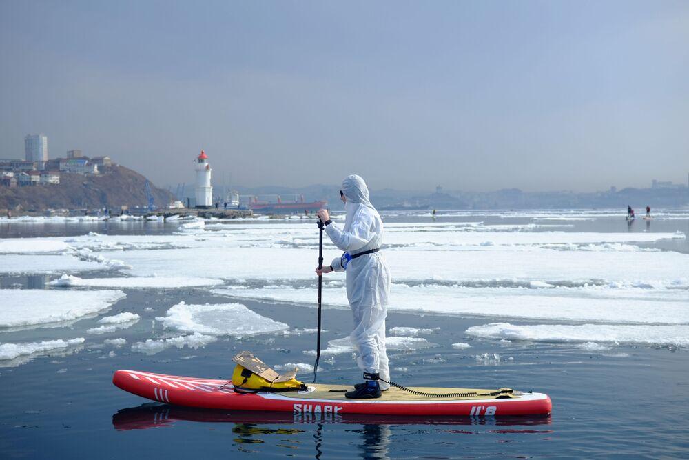 Homem com traje de proteção contra coronavírus sobre prancha em águas de Vladivostok, Rússia, 21 de março de 2020