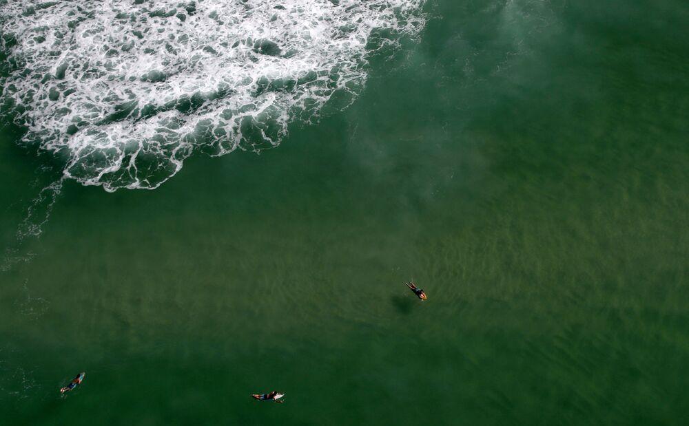 Surfistas na Barra da Tijuca, durante pandemia de COVID-19, no Rio de Janeiro, 26 de março de 2020