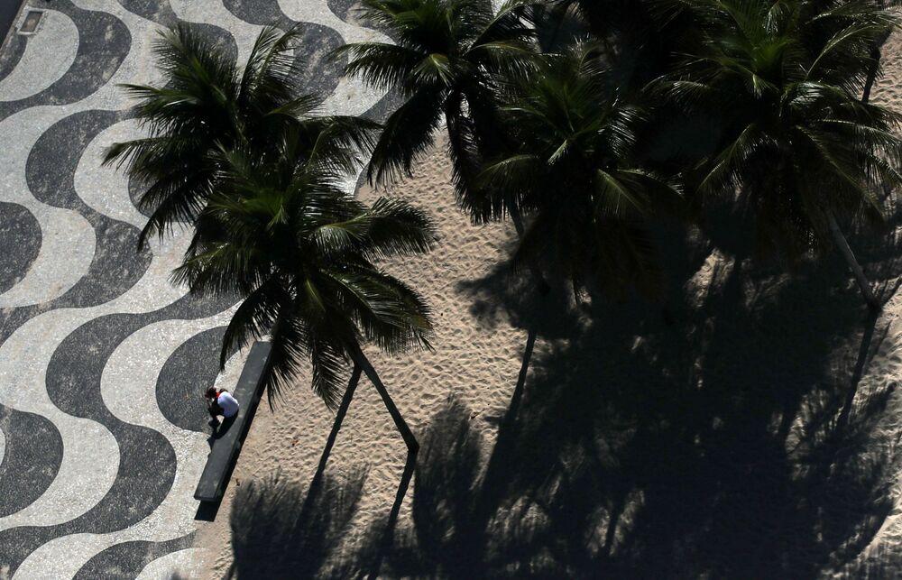 Homem sozinho no calçadão da praia de Copacabana, no Rio de Janeiro, 26 de março de 2020