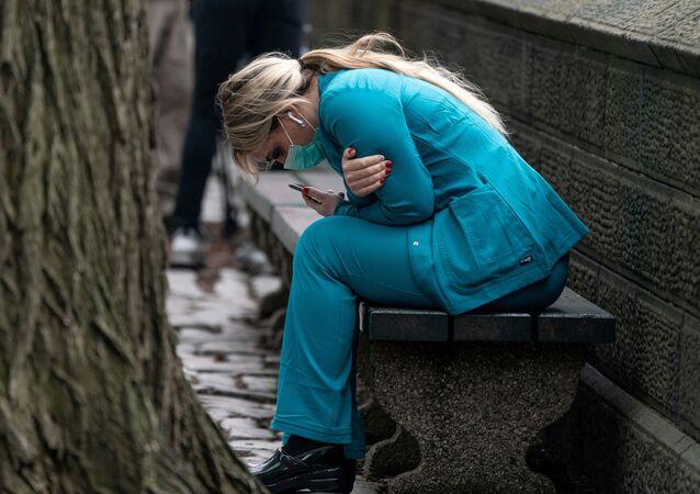 Agente de saúde dos EUA senta em banco no Central Park, em Nova York, 30 de março de 2020