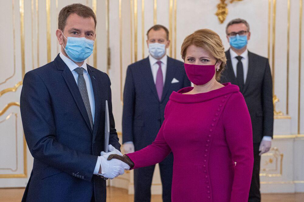 Presidente da Eslováquia, Zuzana Caputova e primeiro-ministro do país, Igor Matovic, usando máscaras de proteção facial no Palácio Presidencial em Bratislava, na Eslováquia, 21 de março de 2020