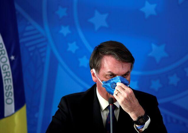 Presidente brasileiro Jair Bolsonaro ajusta sua máscara protetora facial em comunicado à imprensa durante a pandemia de coronavírus, em Brasília, Brasil, 20 de março de 2020
