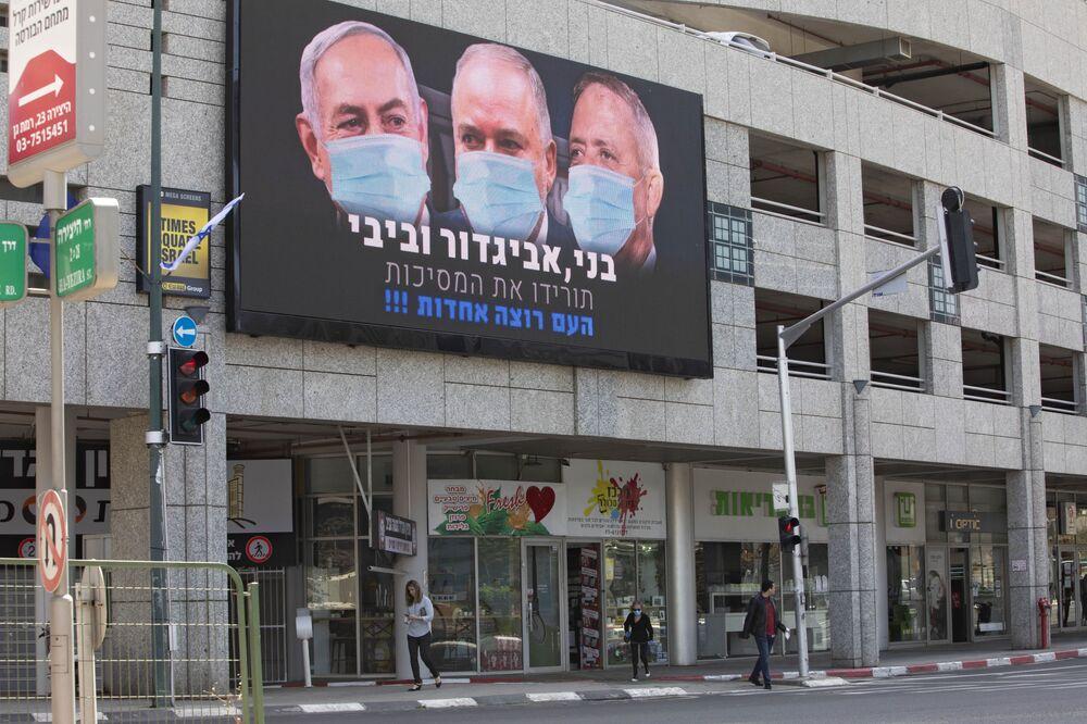 Outdoor mostra o primeiro-ministro israelense Benjamin Netanyahu, o ex-ministro da Defesa israelense Avigdor Lieberman e o líder do partido oposicionista Azul e Branco Benny Gantz usando máscaras em cidade israelense perto de Tel Aviv, 29 de março de 2020
