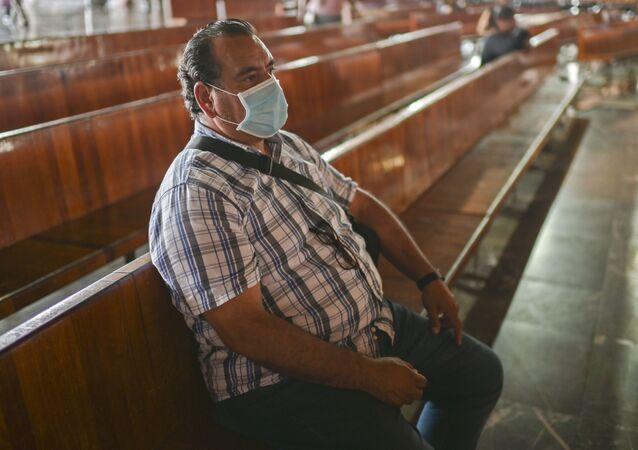 Homem sentado com máscara em igreja no México (foto de arquivo)