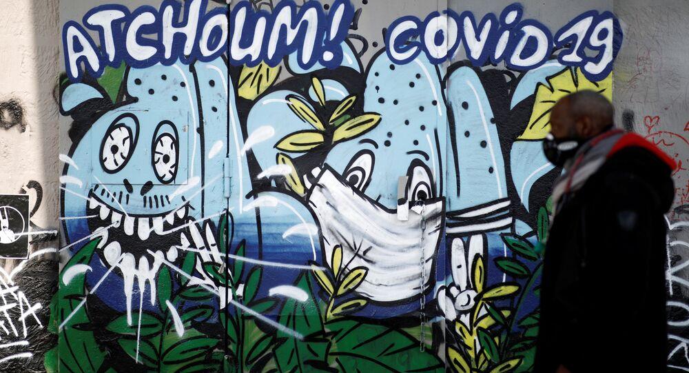 Homem usando máscara protetora passa por um grafite dizendo Espirro COVID-19 em meio ao bloqueio para retardar a propagação da doença do coronavírus (COVID-19) na França, 28 de março de 2020