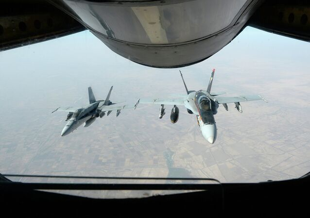 Two U.S. Navy F/A-18E Super Hornet aircraft fly after receiving fuel from an Air Force KC-135 Stratotanker aircraft over Iraq Oct. 4, 2014