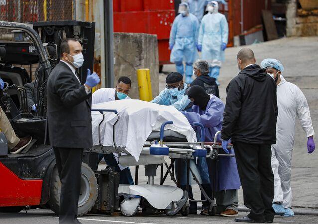 Cadáver de paciente morto pelo coronavírus sendo levado para um caminhão em Nova York, nos EUA