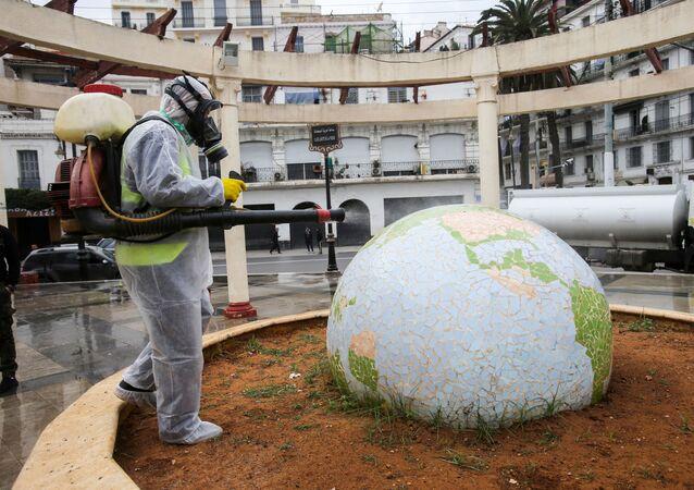 Trabalhador com traje de proteção desinfecta jardim público em forma de globo, em meio à pandemia de coronavírus, em Argel, Argélia, 23 de março de 2020