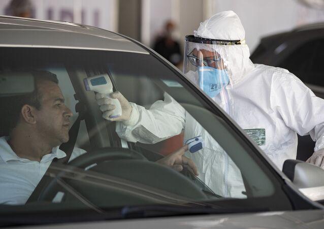 Profissional de saúde checa temperatura de motorista em busca de sintomas da COVID-19 em Guarulhos, na região metropolitana de São Paulo no dia 30 de março.