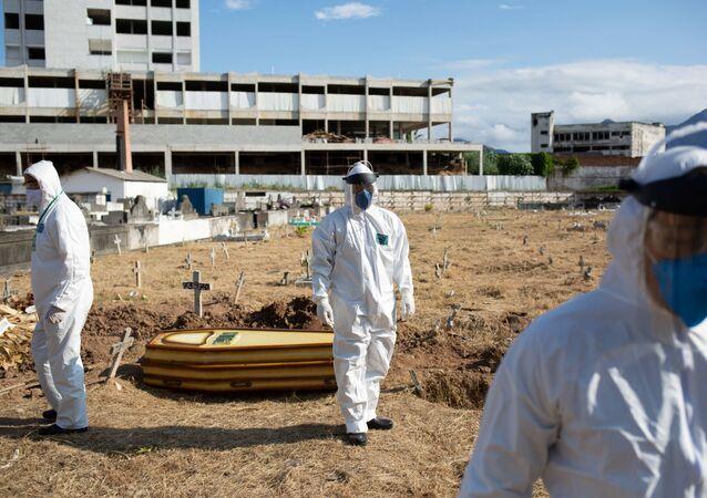 Coveiros com trajes de proteção enterram mortos por razões desconhecidas em meio à pandemia de coronavírus em cemitério no Rio de Janeiro.